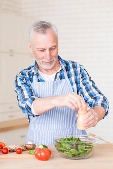 Retrato de un hombre mayor que agrega pimienta con el molino en el tazón de fuente de ensalada verde en la tabla de madera