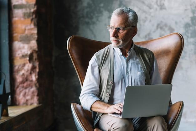 Retrato de un hombre mayor que se sienta en silla con la computadora portátil que mira lejos