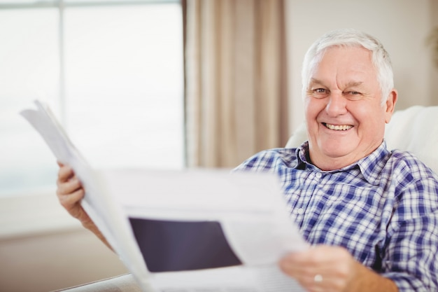 Retrato de hombre mayor sentado en el sofá y leyendo un periódico en la sala de estar