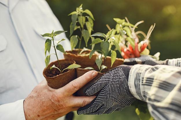 Retrato de hombre mayor con un sombrero de jardinería con granddaugher