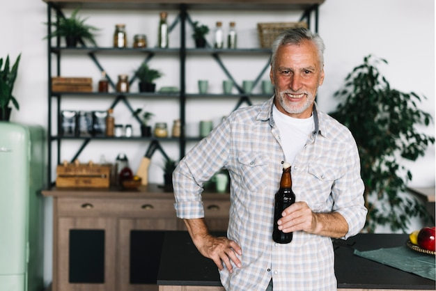 Retrato del hombre mayor sonriente que se coloca en la cocina que sostiene la botella de cerveza