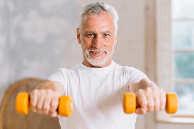 Retrato del hombre mayor sonriente que lleva a cabo pesas de gimnasia