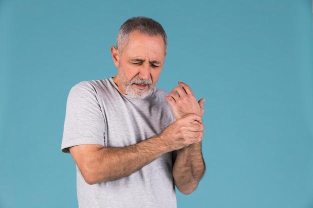 Retrato de un hombre mayor sosteniendo su muñeca lesionada