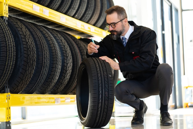 Retrato de hombre mecánico con neumáticos de coche en la estación de servicio. mecánico masculino sosteniendo el neumático de automóvil en la tienda de la tienda de automóviles