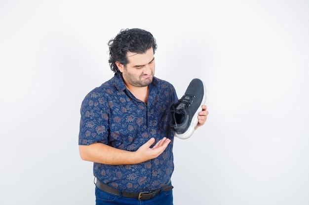 Retrato de hombre de mediana edad presentando zapato en camisa y mirando seria vista frontal