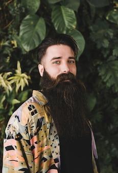 Retrato de un hombre mirando a la cámara frente a las plantas