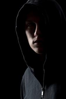Retrato del hombre misterioso en la oscuridad