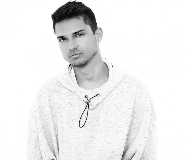 El retrato del hombre modelo hermoso joven se vistió en la ropa con capucha casual gris que presentaba en la pared blanca. aislado