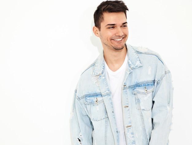 El retrato del hombre modelo joven sonriente hermoso se vistió en la presentación de la ropa de los vaqueros. aislado