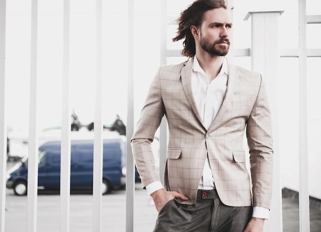 Retrato de hombre de modelo masculino de moda guapo sexy vestido con elegante traje a cuadros beige posando en el fondo de la calle