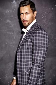 Retrato de hombre de modelo masculino de moda guapo sexy vestido con elegante traje posando junto a la pared gris