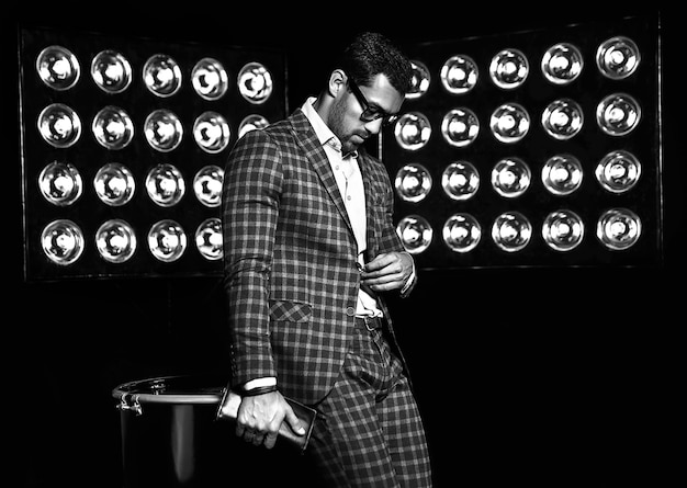 Retrato de hombre de modelo masculino de moda guapo sexy vestido con elegante traje sobre fondo de luces de estudio