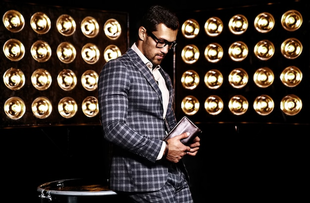 Retrato de hombre de modelo masculino de moda guapo sexy vestido con traje elegante sobre fondo negro de luces de estudio en gafas