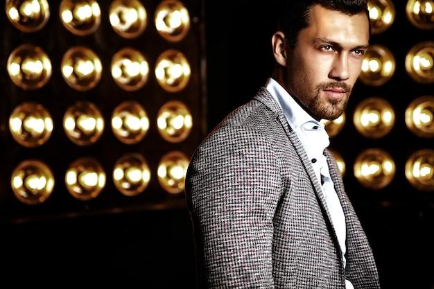 Retrato de hombre de modelo masculino de moda guapo sexy vestido con traje elegante sobre fondo negro de luces de estudio