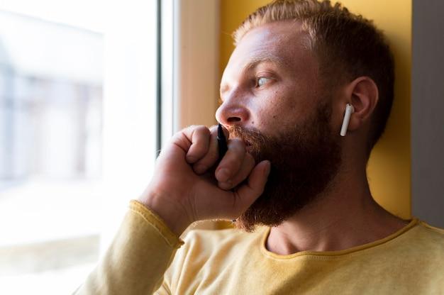 Retrato de hombre moderno mirando pensativo fuera de la ventana