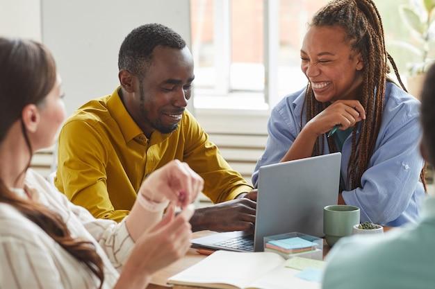Retrato de hombre y mujer afroamericanos riendo alegremente mientras trabaja en un proyecto de equipo con un grupo multiétnico de personas