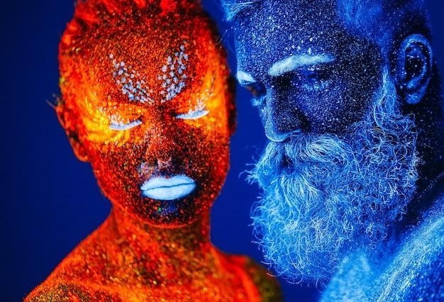 Retrato de un hombre y una mujer con barba pintados en polvo ultravioleta.