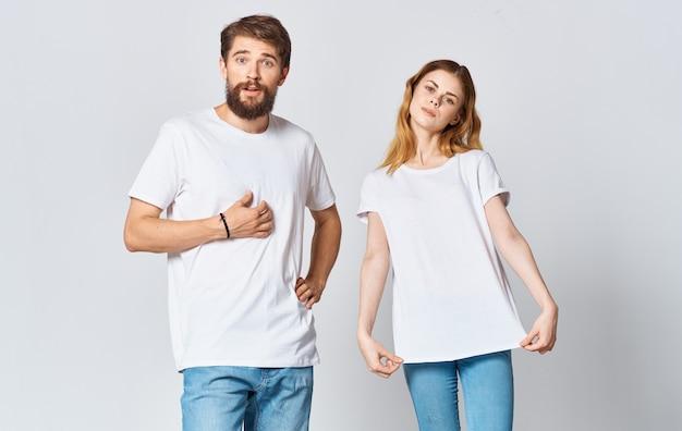 Retrato de un hombre y una mujer en idénticas camisetas adolescente jeans fondo claro. foto de alta calidad