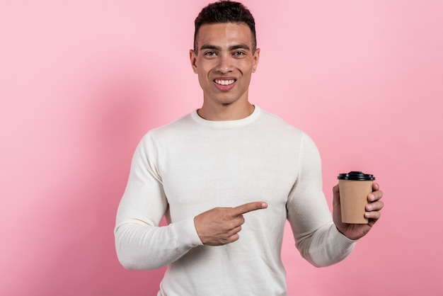 Retrato del hombre mulato alegre feliz que sostiene el vidrio de papel del café