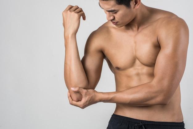 Retrato de un hombre muscular que tiene dolor en el codo aislado sobre fondo blanco