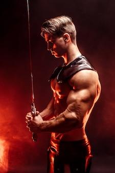 Retrato de hombre musculoso concentrado sexy con espada.