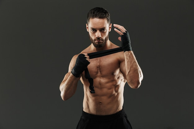Retrato de un hombre musculoso fuerte atar vendas de boxeo