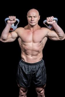 Retrato de hombre musculoso levantamiento kettlebells