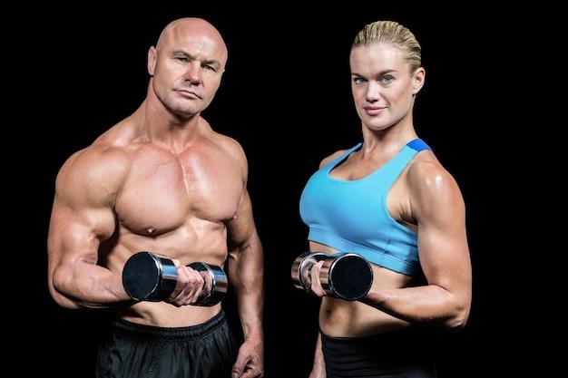 Retrato de hombre musculoso y mujer levantando pesas