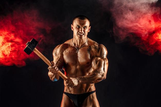 Retrato de hombre musculoso en topless serio con mazo
