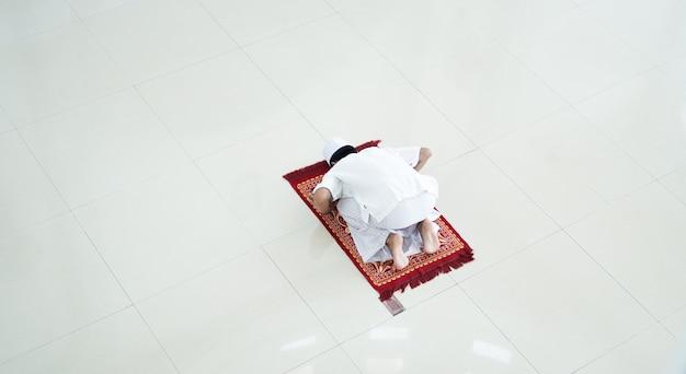 Un retrato de un hombre musulmán asiático reza en la mezquita, el nombre de la oración es sholat, movimiento sujud en sholat