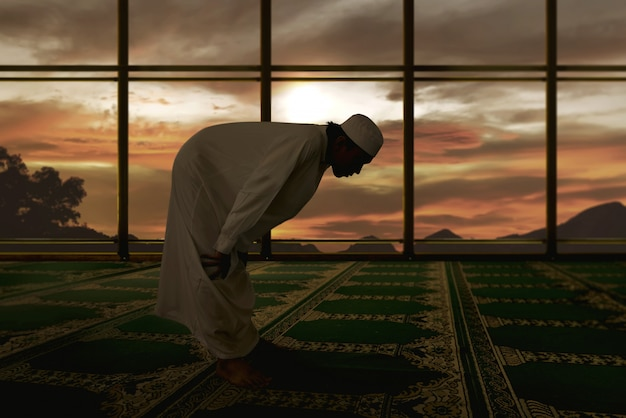 Retrato de hombre musulmán asiático rezando en la mezquita