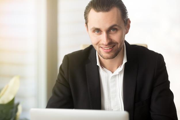 El retrato del hombre de negocios acertado trabaja en la computadora portátil