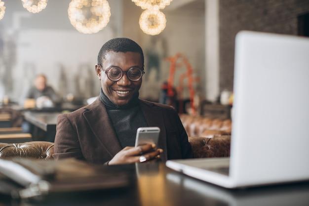 Retrato del hombre de negocios africano feliz que usa el teléfono mientras que trabaja en la computadora portátil en un restaurante.