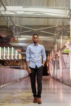 Retrato de hombre de negocios africano negro guapo caminando al aire libre en la ciudad de noche de pie en la pasarela vertical de cuerpo completo