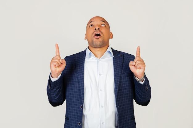 Retrato de hombre de negocios afroamericano joven asombrado, asombrado y sorprendido, mirando hacia arriba y señalando con los dedos y las manos levantadas.