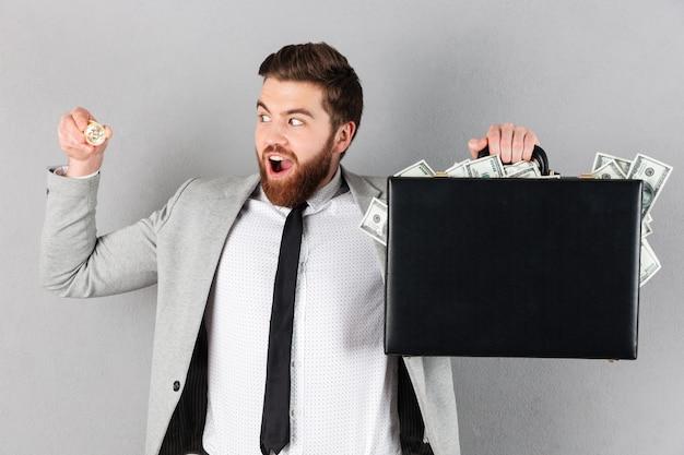 Retrato de un hombre de negocios alegre mostrando bitcoin dorado