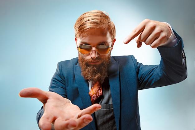 Retrato de un hombre de negocios apuntando con su dedo a la otra mano