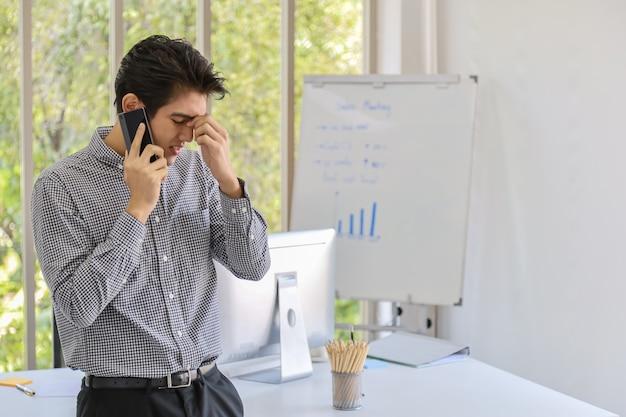 El retrato del hombre de negocios asiático joven elegante hace una llamada telefónica y siente preocupación con el teléfono móvil elegante con el escritorio de la computadora, el tablero de la reunión y los accesorios.