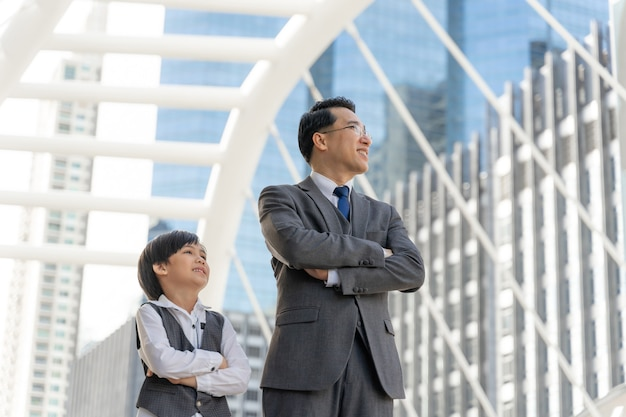 Retrato de hombre de negocios asiático y su hijo en el distrito de negocios