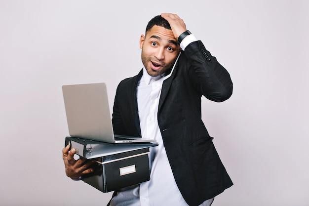 Retrato de hombre de negocios atractivo trabajador con caja de oficina, carpetas, portátil hablando por teléfono. trabajador de oficina, gerente inteligente, malentendido, tarde, perdido.