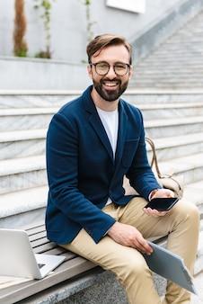 Retrato de hombre de negocios complacido con anteojos sosteniendo portapapeles y teléfono celular mientras está sentado en un banco cerca de las escaleras