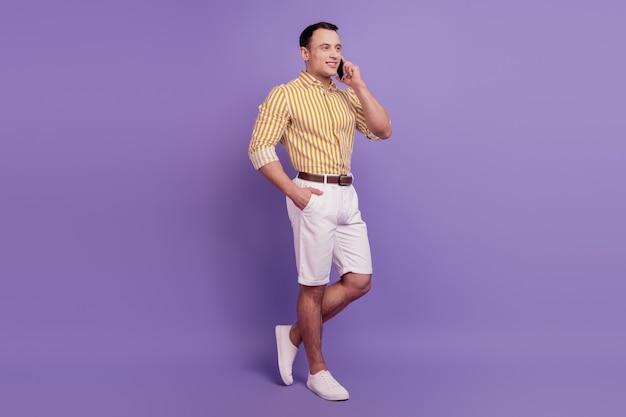 Retrato de hombre de negocios confiado hablar por teléfono sobre fondo violeta