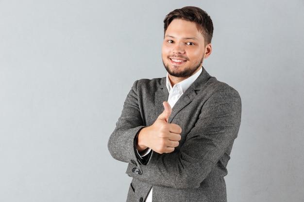 Retrato de un hombre de negocios confidente que muestra los pulgares para arriba