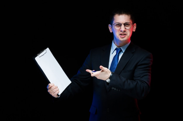Retrato de hombre de negocios elegante guapo confiado con portapapeles en sus manos negro