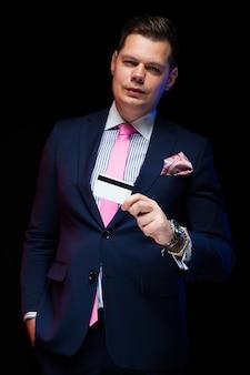 Retrato del hombre de negocios elegante hermoso confiado que sostiene la tarjeta de crédito en su mano en negro