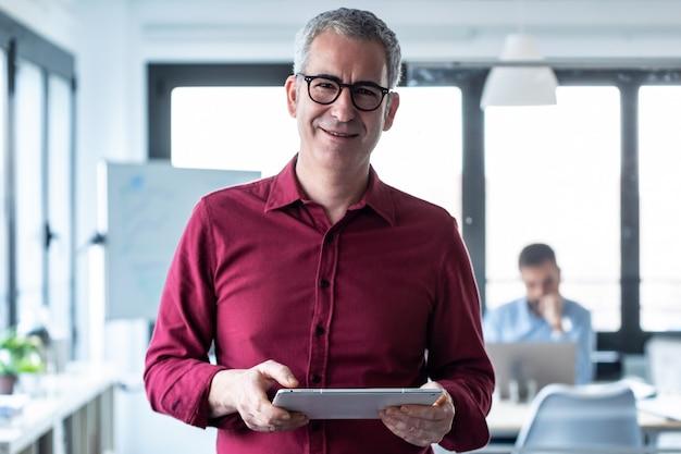 Retrato de hombre de negocios elegante mirando a cámara mientras trabaja con tableta digital en la oficina.