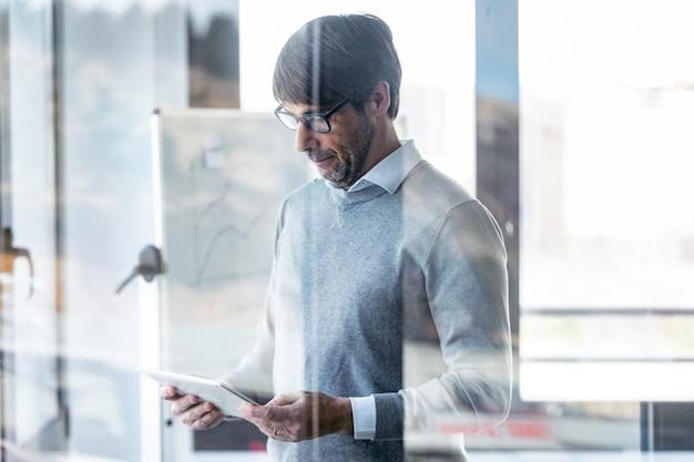 Retrato de hombre de negocios elegante trabajando con tableta digital en la oficina.
