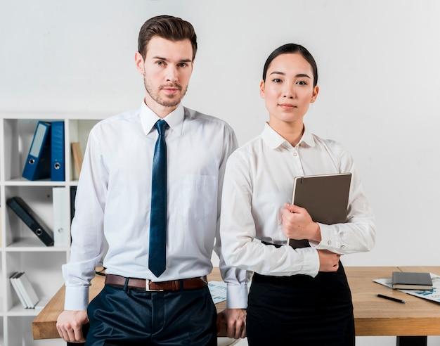Retrato del hombre de negocios y de la empresaria jovenes confiados que se colocan delante del escritorio