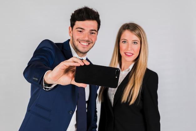 Retrato de un hombre de negocios y de una empresaria jovenes que toman el selfie en el teléfono móvil contra fondo gris