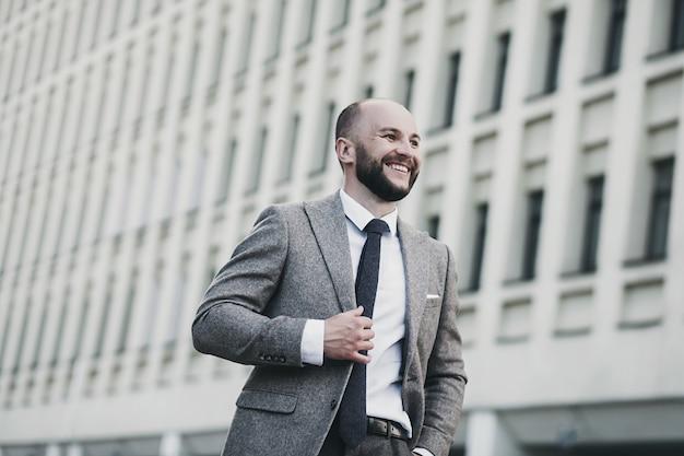 Retrato de un hombre de negocios de éxito positivo en un traje en el fondo de un edificio